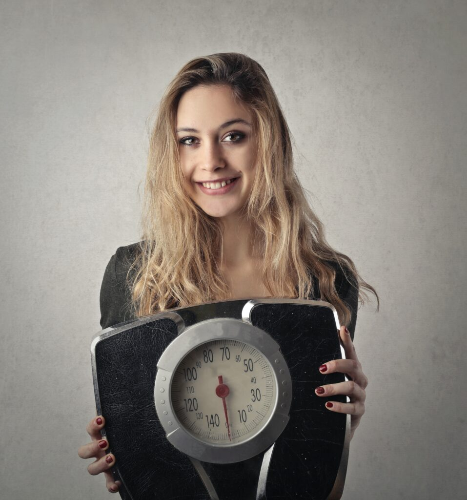 young woman smiling and holding a scale