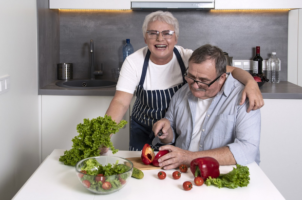 older woman and man cutting vegetables in kitchen